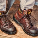 closeup image of two dark brown leather caterpillar brand work boots