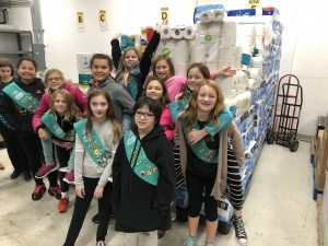 Girl Scouts with toilet paper donation.