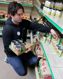 Local musician Anthony Worden stocks shelves at CommUnity Food Bank during his volunteer shift.