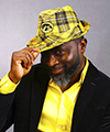 Photo of Eddie Etsey wearing a Hawkeyes fedora in front of a grey background.